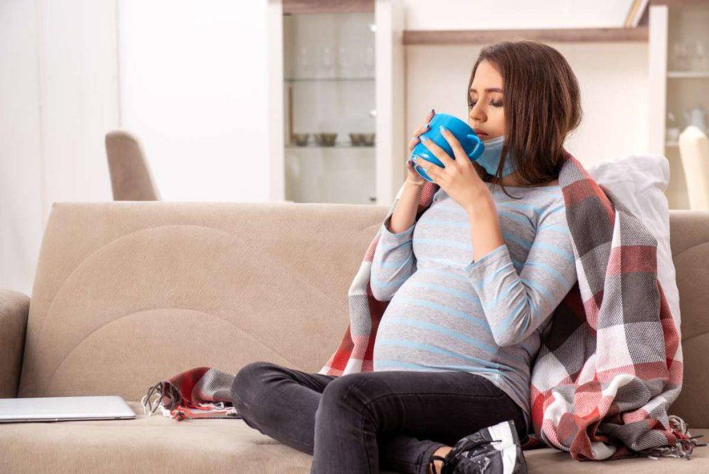 chorá tehotná žena pije čaj na gauči