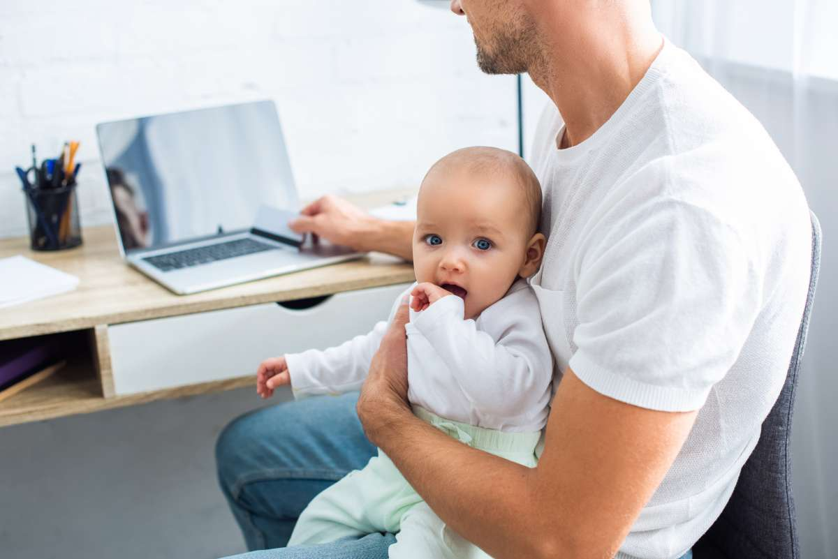 otecko s batoľaťom na kolene premýšľa nad nákupom cez počítač