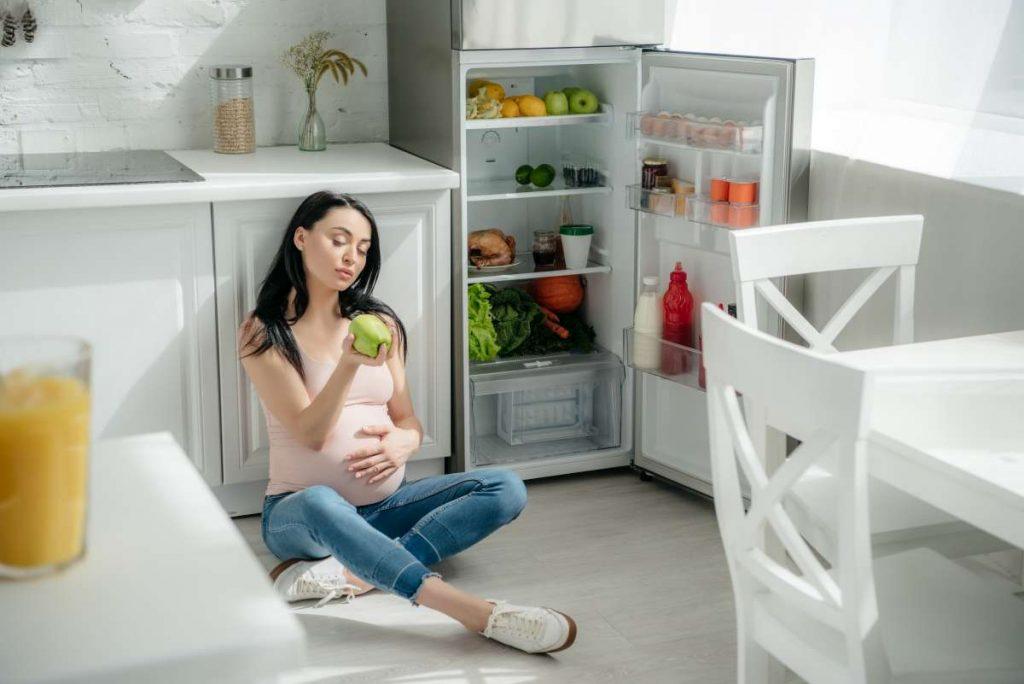 tehotná žena sedí vedľa otvorenej chladničky a v ruke drží jablko