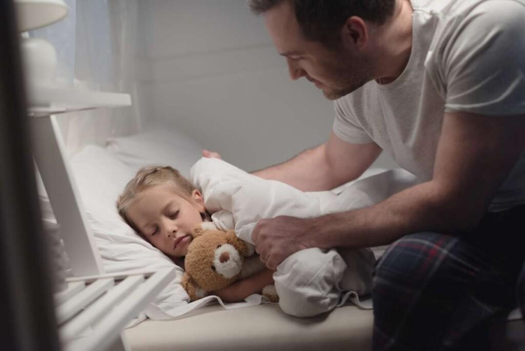 otecko uspáva dcérku v posteli