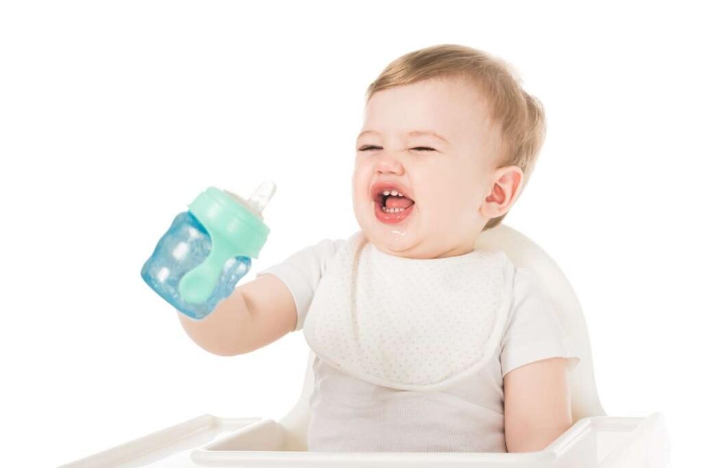 dieťa je nespokojné s fľašou v ruke