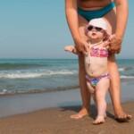 mama kráča s batoľaťom po pláži