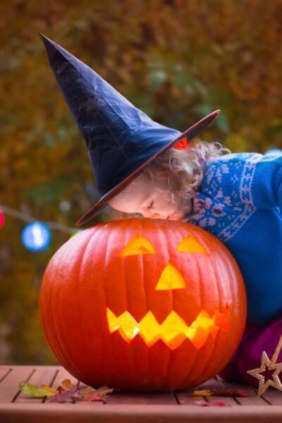 dievča v čarodejníckej čiapke nazerá do vyrezanej tekvice