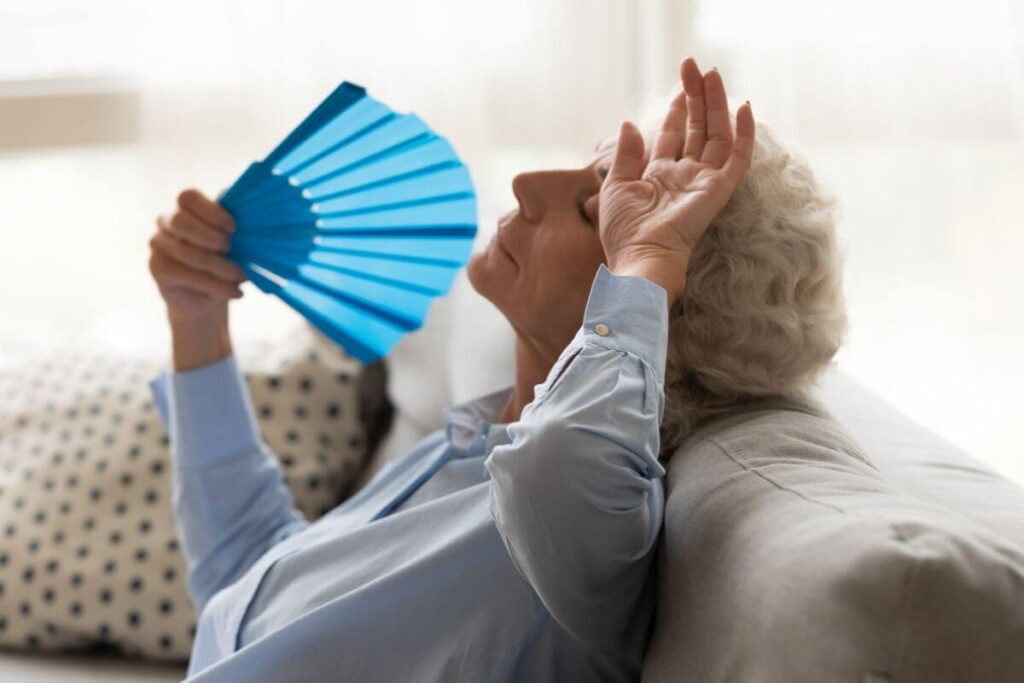 seniorná dáma sa cíti na odpadnutie a ovieva sa vejárom