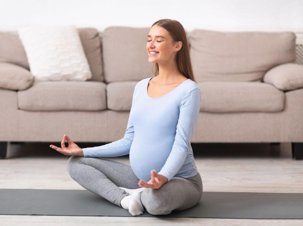 tehotná žena sedí vzpriamene na zemi a usmieva sa pri meditácii